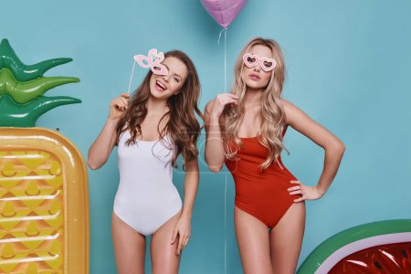 Two playful young women in swimwear looking at camera and holding party glasses