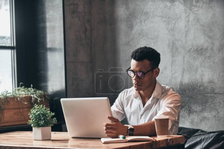 Photo for Concentrated handsome young African man in eyewear working with laptop while sitting in office - Royalty Free Image
