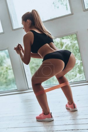 Rear view of young woman in sport clothing crouching using resistance band while exercising in the gym