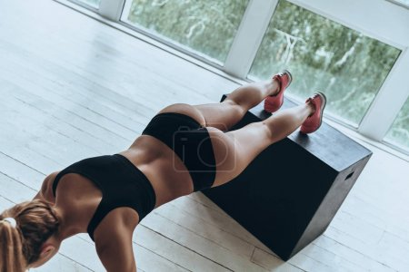 Top view of young woman in sport clothing keeping plank position while exercising in the gym