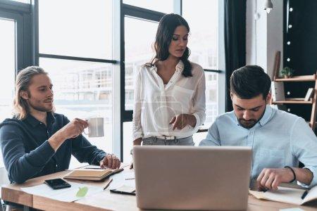 Arbeitstag. junge moderne Kollegen in schicker Freizeitkleidung arbeiten zusammen, während sie Zeit im kreativen Büro verbringen