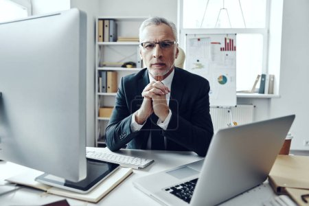 Photo pour Senior man in elegant business suit using modern technologies and looking at camera while working in modern office - image libre de droit