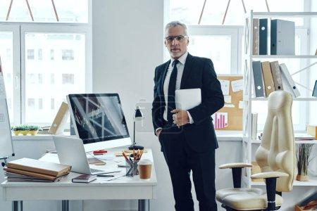 Photo pour Senior trader en costume d'affaires élégant en utilisant une tablette numérique tout en travaillant au bureau - image libre de droit