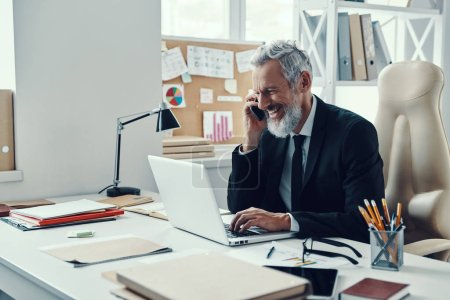 Photo pour Happy mature man in full suit using laptop and talking on the phone while working in modern office - image libre de droit