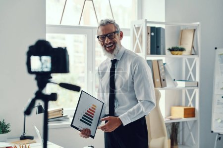 Photo pour Happy mature man in elegant shirt and tie showing chart and sharing business experience while making social media video - image libre de droit