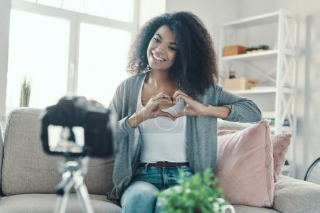 Photo for Cute young African woman showing heart with her hands and smiling while making social media video - Royalty Free Image