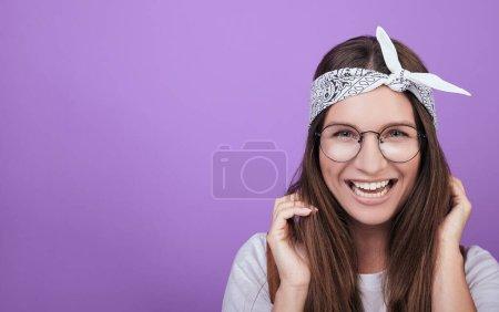 Photo pour Une fillette mignonne aux cheveux foncés en bandage sur la tête dans un T-shirt blanc, des verres ronds lui tiennent les cheveux et rient. Couche droite. Portrait en gros plan. Photo sur le fond. - image libre de droit