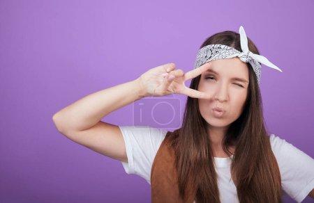 Photo pour Une jeune femme vêtue d'un T-shirt blanc, d'une veste brune et d'un bandeau montre un signe de paix et fait un baiser. Photo en arrière-plan. Paix pour la paix. Pacifisme. - image libre de droit
