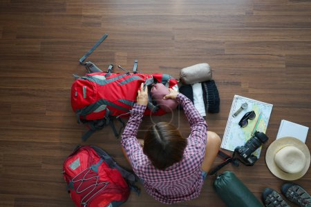 Photo for Overhead view of traveler woman plan and backpack planning vacation trip with map. Top view. - Royalty Free Image