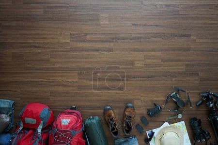 Photo for Overhead view of Traveler's accessories, trip vacation, tourism mockup, backpack, camera, drone, shoes with map on wooden table background, top view - Royalty Free Image