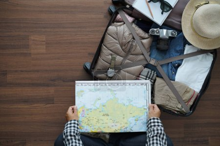 Photo for Overhead view of traveler woman plan and backpack planning vacation trip with map. Top view on wooden floor - Royalty Free Image