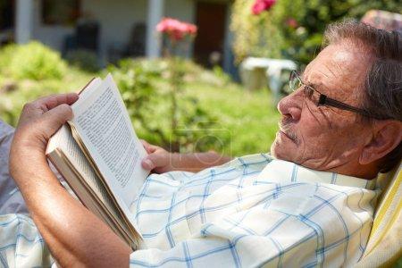 Foto de Senior man reading outdoor - Imagen libre de derechos