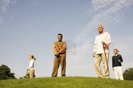 Photo pour Vue à angle bas de deux hommes et de deux femmes debout sur un terrain de golf - image libre de droit