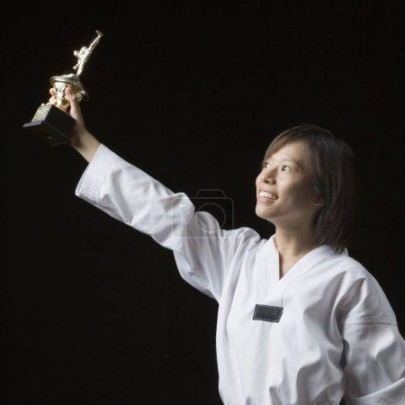 Photo pour Jeune femme levant un trophée et souriant - image libre de droit