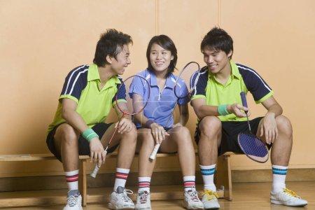 Photo pour Deux jeunes hommes et une jeune femme assis côte à côte sur un banc et tenant des raquettes de badminton - image libre de droit