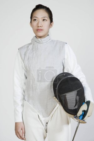 Photo pour Gros plan d'une femme escrimeuse tenant une feuille de clôture et un masque de clôture - image libre de droit