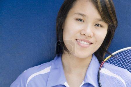 Photo pour Portrait d'une jeune femme portant une raquette de badminton et souriant - image libre de droit
