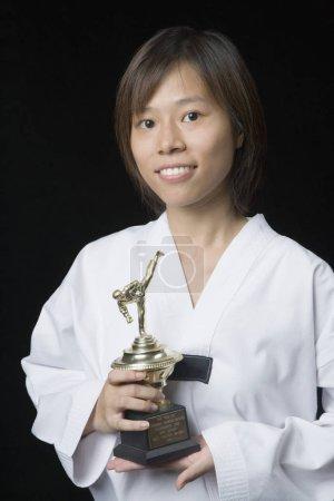 Photo pour Portrait d'une jeune femme tenant un trophée et souriante - image libre de droit