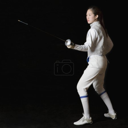 Photo pour Profil latéral d'une femme escrimeuse tenant une feuille de clôture - image libre de droit