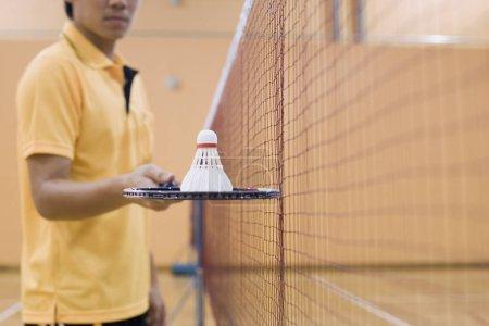Photo pour Vue en plein milieu d'un jeune homme debout dans un court de badminton tenant une raquette de badminton - image libre de droit