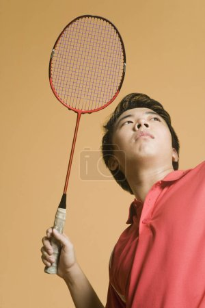 Photo pour Gros plan sur un jeune homme jouant au badminton - image libre de droit