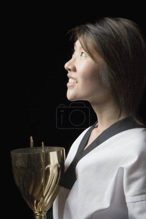 Photo pour Profil latéral d'une jeune femme tenant un trophée - image libre de droit
