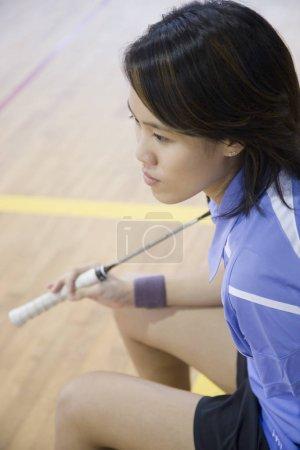 Photo pour Vue à grand angle d'une jeune femme tenant une raquette de badminton - image libre de droit