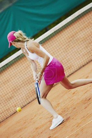 Photo pour Profil latéral d'une femme d'âge moyen jouant au tennis - image libre de droit