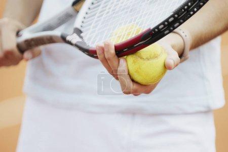 Photo pour Vue en milieu de section d'une joueuse de tennis tenant une raquette et une balle de tennis - image libre de droit