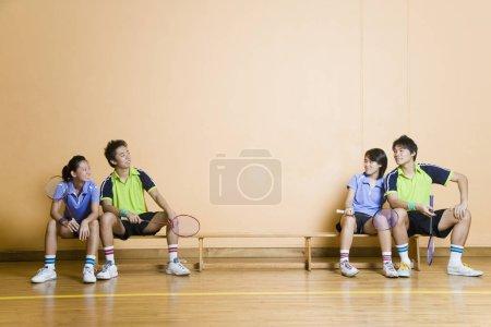 Photo pour Deux jeunes couples assis sur un banc et tenant des raquettes de badminton - image libre de droit