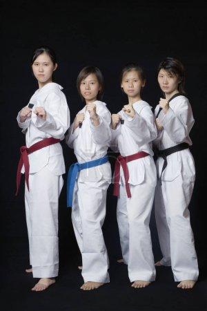Photo pour Quatre jeunes femmes se tenant debout en position de poinçonnage - image libre de droit