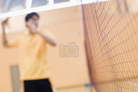 Photo pour Jeune homme jouant dans un tribunal de badminton - image libre de droit