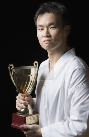 Photo pour Portrait d'un jeune homme tenant un trophée - image libre de droit