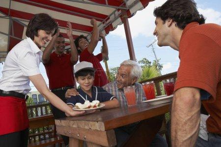 Foto de Boy celebrando su cumpleaños con su padre y abuelo en un restaurante. - Imagen libre de derechos
