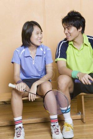 Photo pour Jeune couple assis sur un banc et tenant des raquettes de badminton - image libre de droit