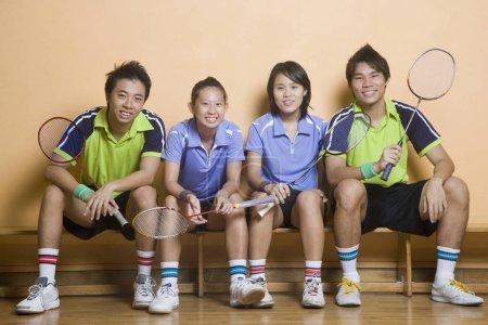 Photo pour Portrait de deux jeunes femmes et de deux jeunes hommes assis côte à côte sur un banc et tenant des raquettes de badminton - image libre de droit