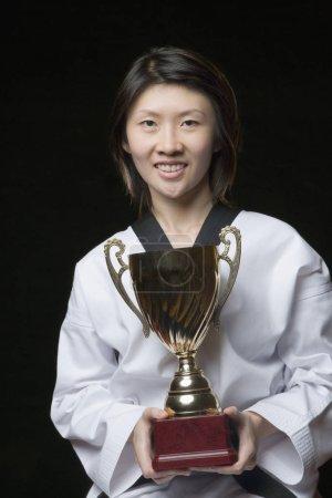 Photo pour Portrait d'une jeune femme tenant un trophée - image libre de droit