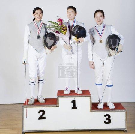 Photo pour Portrait de trois jeunes femmes en costumes d'escrime debout sur le podium d'une gagnante - image libre de droit