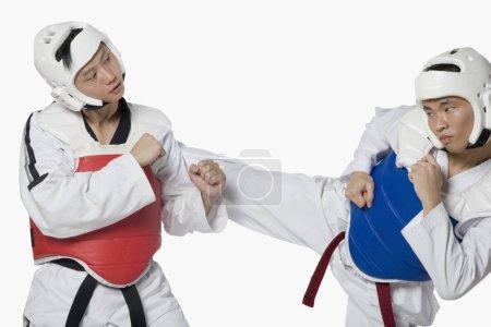 """Photo pour Gros plan d'un homme d """"âge moyen qui pratique la kickboxing avec un jeune homme - image libre de droit"""