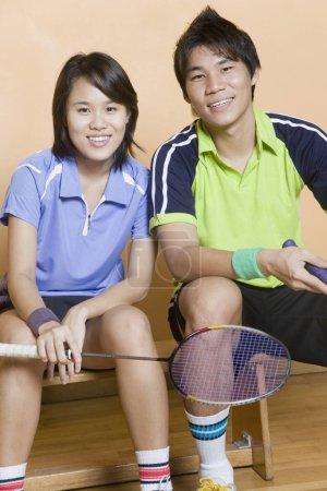 Photo pour Portrait d'un jeune couple assis sur un banc tenant des raquettes de badminton - image libre de droit