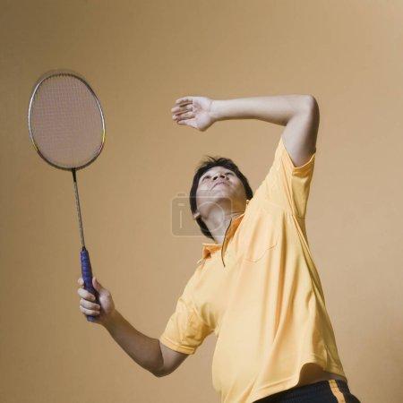 Photo pour Jeune homme jouant au badminton - image libre de droit