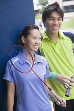 Photo pour Gros plan d'un jeune couple tenant des raquettes de badminton et souriant - image libre de droit