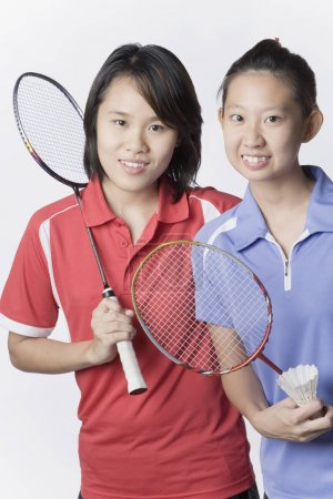 Photo pour Portrait de deux jeunes femmes tenant des raquettes de badminton et souriant - image libre de droit