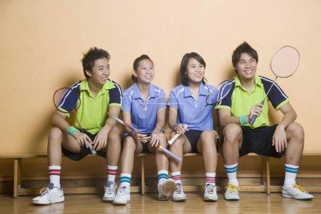 Photo pour Deux jeunes femmes et deux jeunes hommes assis côte à côte sur un banc et tenant des raquettes de badminton - image libre de droit