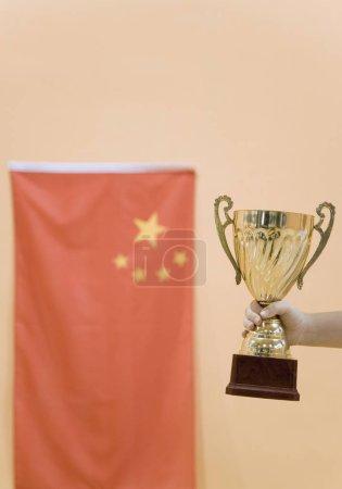 Photo pour Gros plan sur la main d'une personne tenant une coupe de trophée en or - image libre de droit