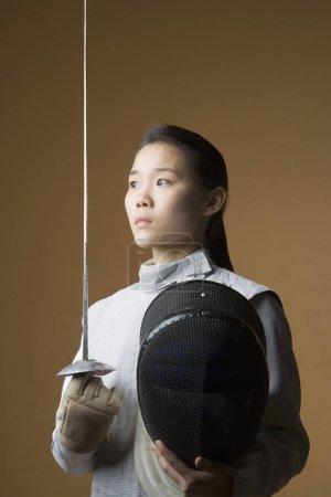 Photo pour Gros plan d'une femme escrimeuse tenant une épée et un masque d'escrime - image libre de droit