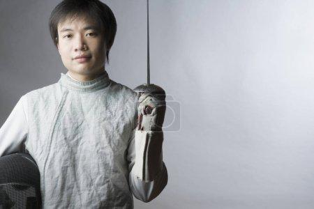 Photo pour Portrait d'un homme portant une épée et un masque d'escrime - image libre de droit