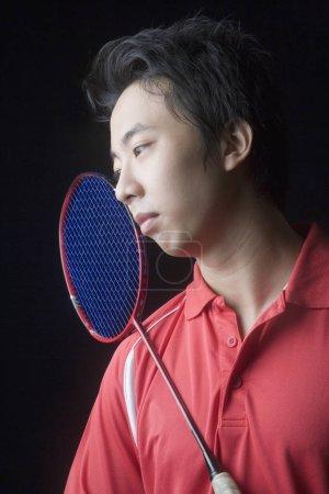 Photo pour Gros plan sur un jeune homme portant une raquette de badminton - image libre de droit