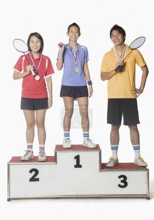 Photo pour Portrait de deux jeunes femmes et d'un jeune homme debout sur le podium et vêtus d'une médaille sportive - image libre de droit