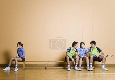 Photo pour Deux jeunes hommes et une jeune femme assis côte à côte sur un banc avec une autre jeune femme assise à l'autre coin - image libre de droit